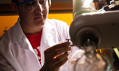 Student examining microscope.