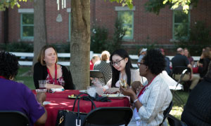 Women eating outside during the alumni picnic.