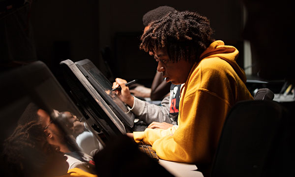 Student drawing on a Wacom tablet.