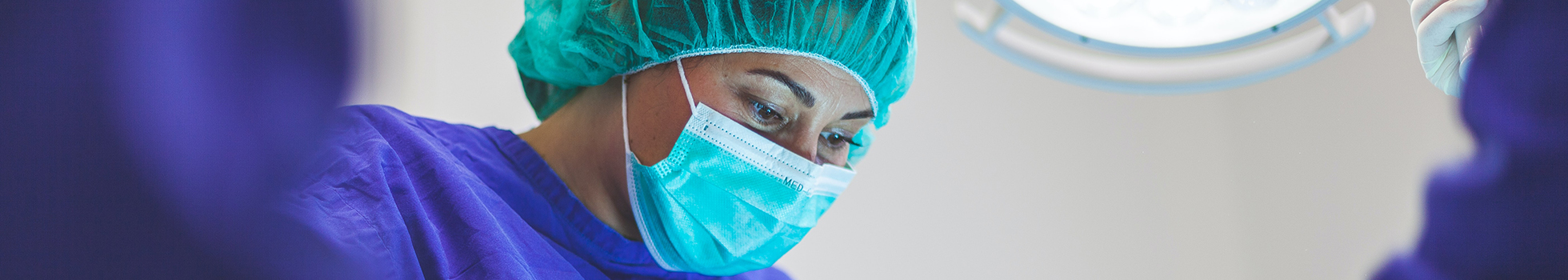 Woman in scrubs and mask.