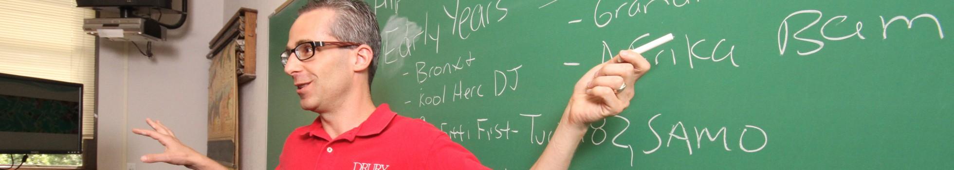 Rich Schur teaching at a chalk board.