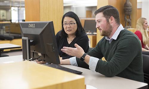 A man and women working together on a computer.