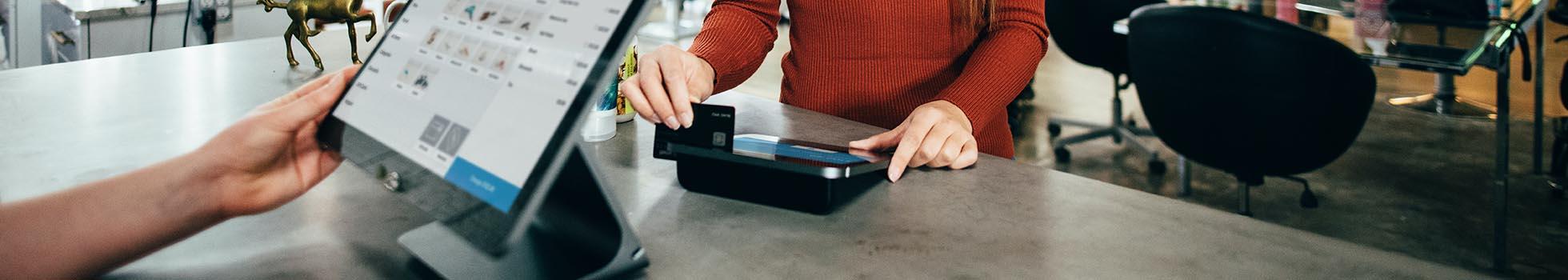 Woman swiping a credit card.