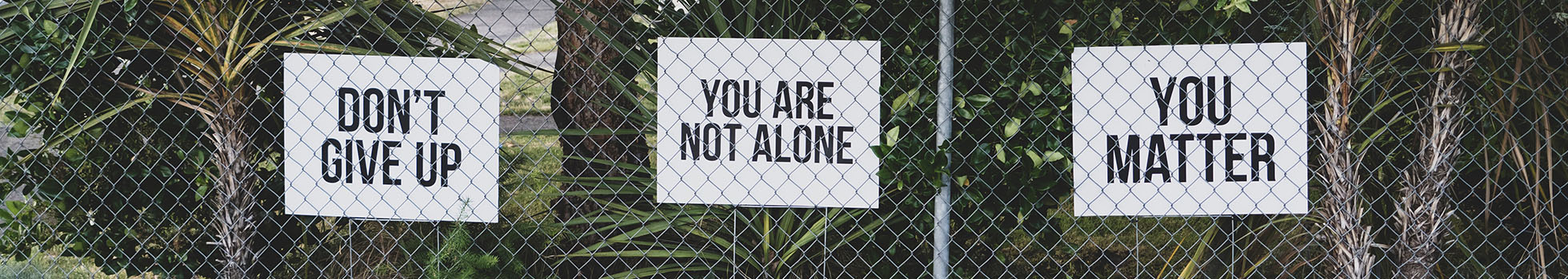 Fence with signs saying don't give up, you matter, and you are not alone.