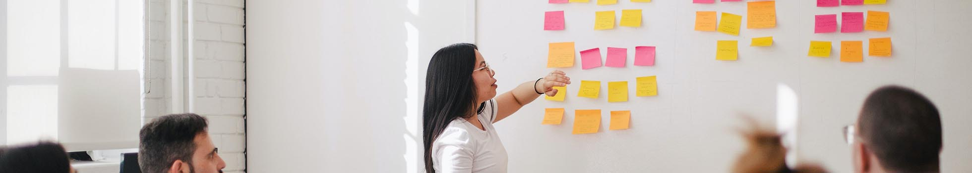 Woman standing in front of a whiteboard with post-it notes.
