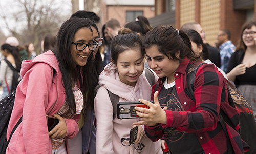 Students looking at a cell phone.