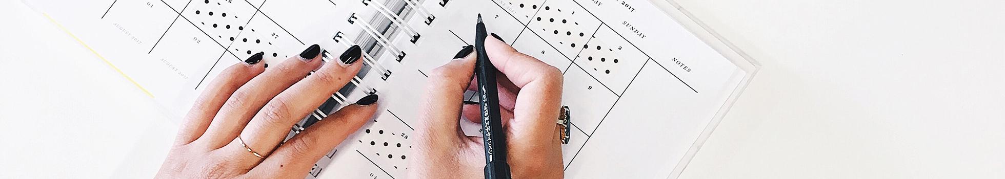 Woman writing a schedule on a calendar.