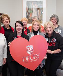 Drury alumni standing with a Drury University heart.