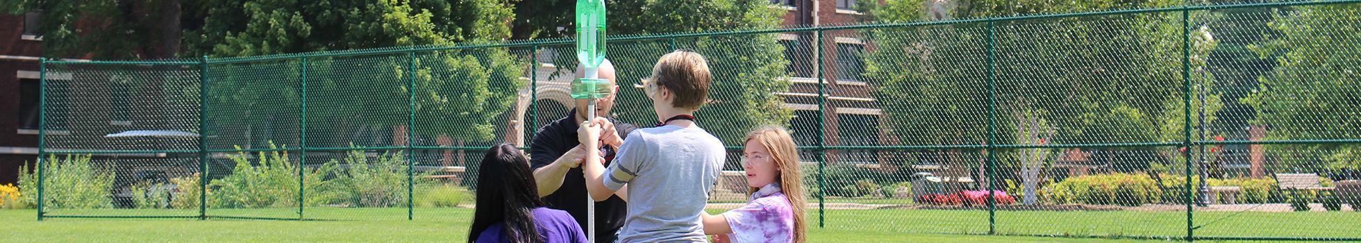 Teacher with kids using bottles as rockets.